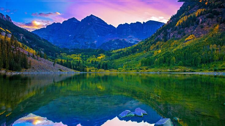 A stunning sunset over Colorado mountains behind a glistening lake