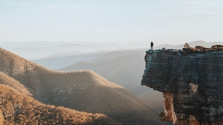 A man on top of a cliff overlooking Kanangra-Boyd National Park, NSW, for his Queen's Birthday Weekend getaways