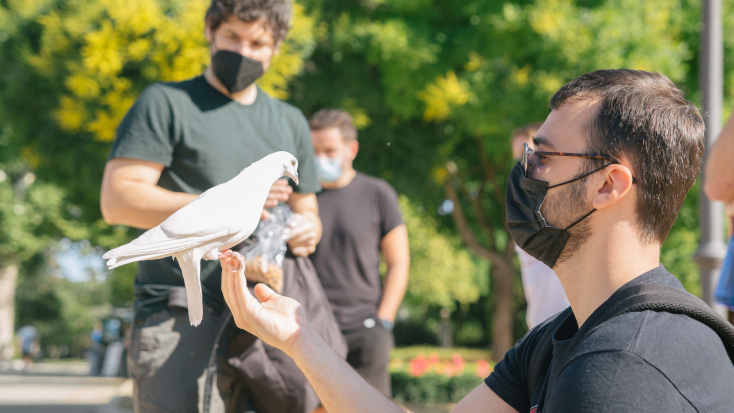 Glamping Hub's team member holding a pigeon as a challenge during their team building sports day