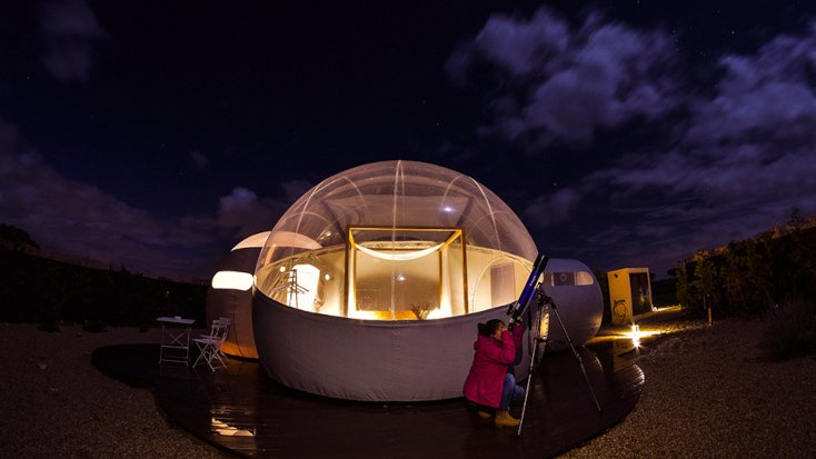 A guest star gazing using a telescope at the bubble dome luxury hotel in spain.